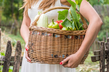 Young woman with the basket full of vegetables