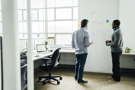 Businessmen using whiteboard in office