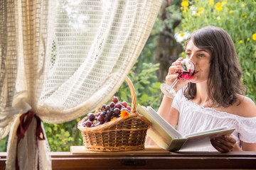 Young woman in a window frame with  wine , graes and book