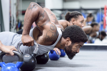 Man and women doing push-ups with kettlebells