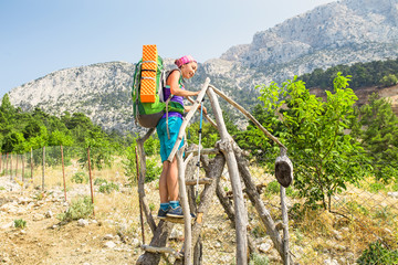 Tourists with a large backpack are climbing through the village fence while traveling along the Lycian Way in the background of Mount Tahtali, Turkey