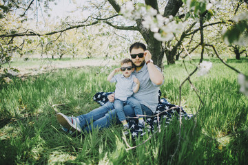 Caucasian father and son wearing sunglasses on blanket in grass