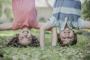 Hispanic brother and sister doing headstands in grass