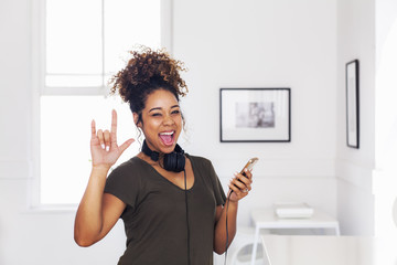 Mixed race woman gesturing and holding cell phone