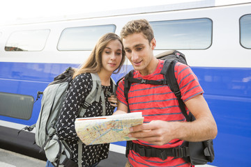 Caucasian couple reading math near train