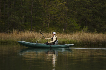 Caucasian man fishing on kayak