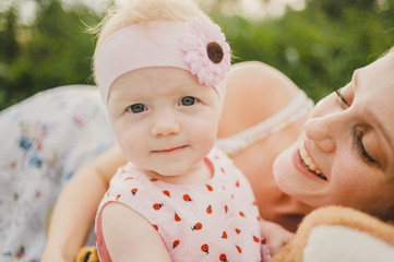 Mother posing with baby daughter wearing headband