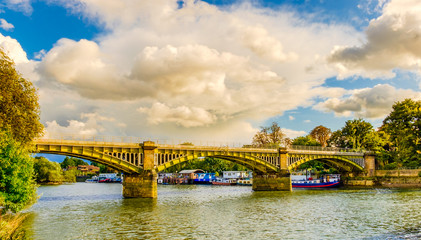Boats moored by Twickenham Bridge spanning over the river Thames, London U.K Wall mural
