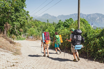A group of three modern tourists backpackers travels in the summer along the Lycian Way in Turkey