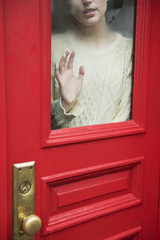 Caucasian woman daydreaming behind red door