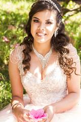 Smiling Hispanic girl wearing gown holding flower