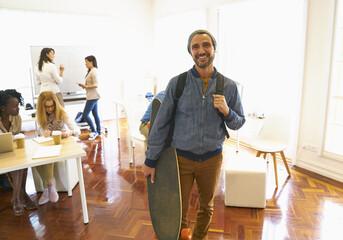 Portrait of man holding skateboard in office