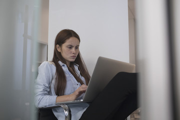 Young woman working on laptop indoors