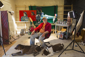 Portrait of older Caucasian man in workshop with dogs
