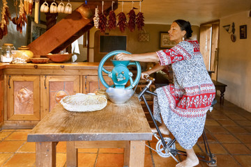 Woman pedaling to power grinder in kitchen