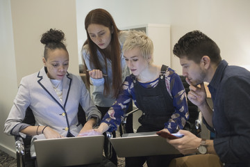 Group of young professionals collaborating in office with their laptops