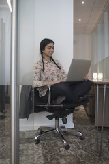 Young woman sittin cross-legged in office typing on her laptop.