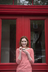 Caucasian woman holding a cupcake near red doorway