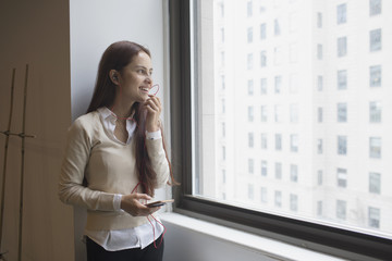 Smiling young woman talking on smartphone while looking through window