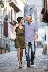 Caucasian couple hugging while walking in city