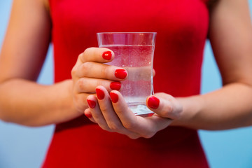 Glass of water in woman's hands with red manicure