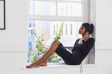 Mixed Race woman sitting in windowsill listening to headphones
