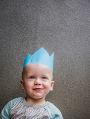 Caucasian baby boy wearing blue paper crown