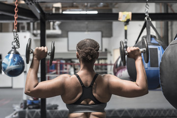 Rear view of woman lifting dumbbells in gym