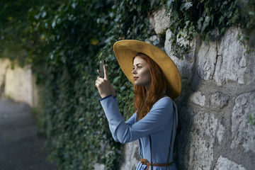 Caucasian woman photographing with cell phone near stone wall