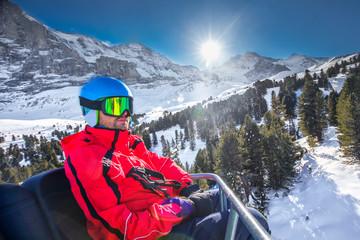 Young skier on ski lift in famous Ski resort in Tyrolian Alps, Zillertal, Austria