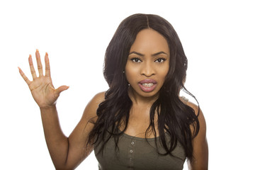 Black female isolated on a white background displaying Angry facial expressions.  She is young and of African American ethnicity.