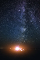 Illuminated tent on the beach against the background of a bright sky with milky way