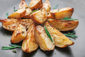 Delicious baked potatoes with rosemary on plate