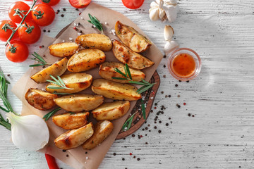 Board with delicious baked potatoes with rosemary on table