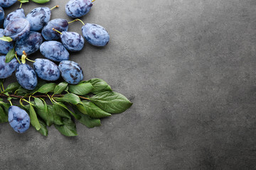 Fresh ripe plums with leaves on grey background
