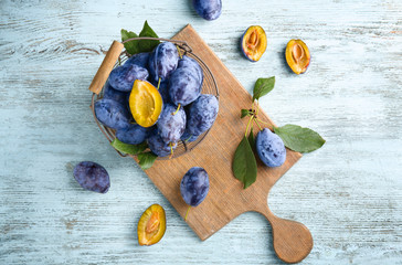 Basket with ripe plums on wooden background
