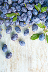 Fresh ripe plums on wooden background