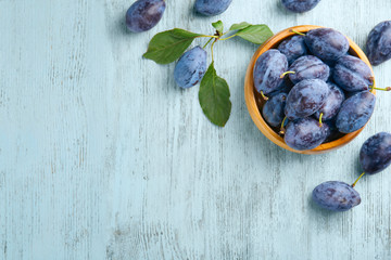 Bowl with ripe plums on wooden background