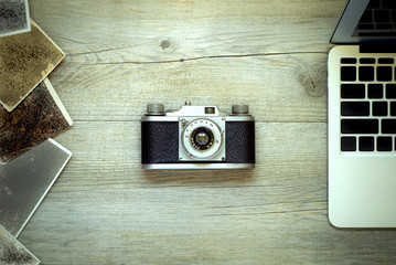 Flat view of vintage rangefinder film photo camera, with some unidentified pictures and notebook on a rustic wooden table. Concept background for working in digital design and post production editing