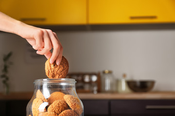 Poster Koekjes Woman taking oatmeal cookie from glass jar