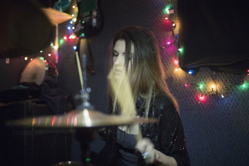 Young woman playing drums at band rehearsal