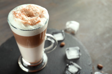 Glass with caramel macchiato and ice cubes on slate plate