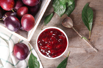 Bowl of delicious plum jam on table