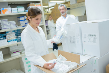 smiling attractive young female pharmacist at work