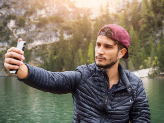 Young handsome man taking selfie with smartphone at lake in forest.