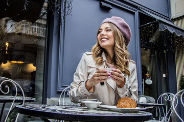 Cheerful french woman. Low-angle view of beautiful blonde woman in beret looking away and smiling while sitting in french vintage cafe. Woman drinking coffee with croissant. French breakfast concept. Wall mural
