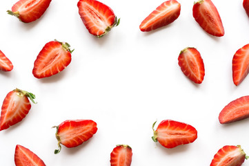 Strawberry pattern with copy space. Sliced ripe red berry on white background. Overhead view.