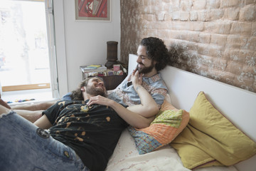 Gay couple lying on their bed together