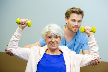 elderly female is engaged with dumbbells in modern sports hall