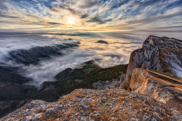 Beautiful scenic autumn blue sky sunset landscape of cloud shroud covered Western Caucasus mountain forest. Scenery viewed from top of Bolshoy Tkhach rocky mountain. Russia